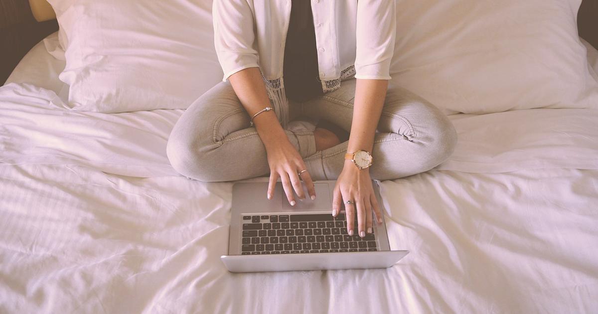 Henkilö istuu vuoteella kannettavan tietokoneen kanssa.