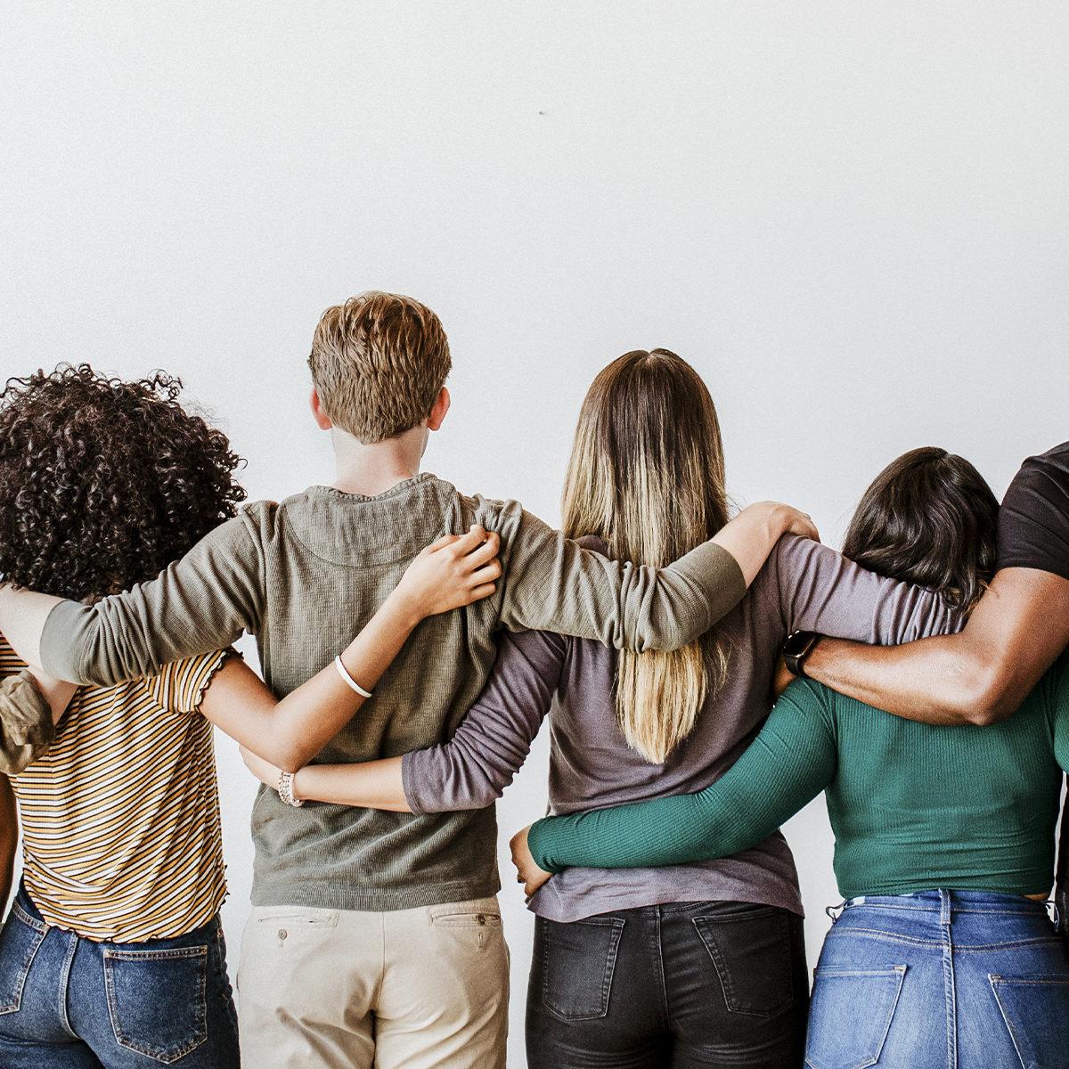 Erilaisia ihmisiä seisomassa vierekkäin toisiaan tukien