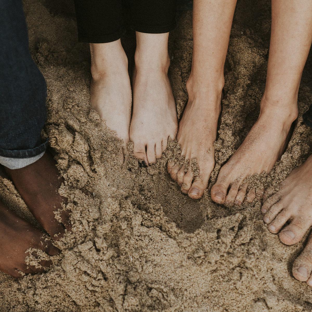 Monet erilaiset jalat hautautuneina rantahiekkaan