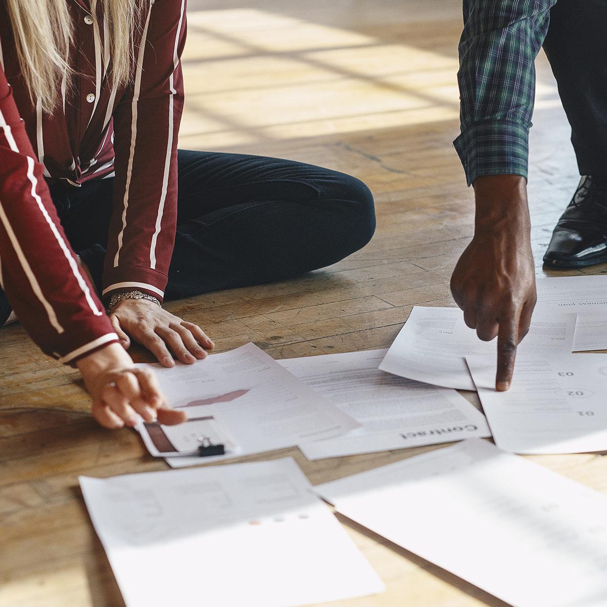 Kaksi henkilöä istumassa lattialla ja läpikäymässä yhdessä virallisia papereita
